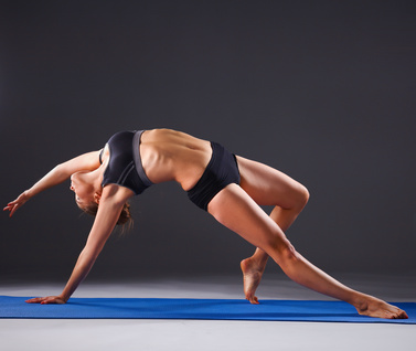 Young woman doing yoga exercise on mat .