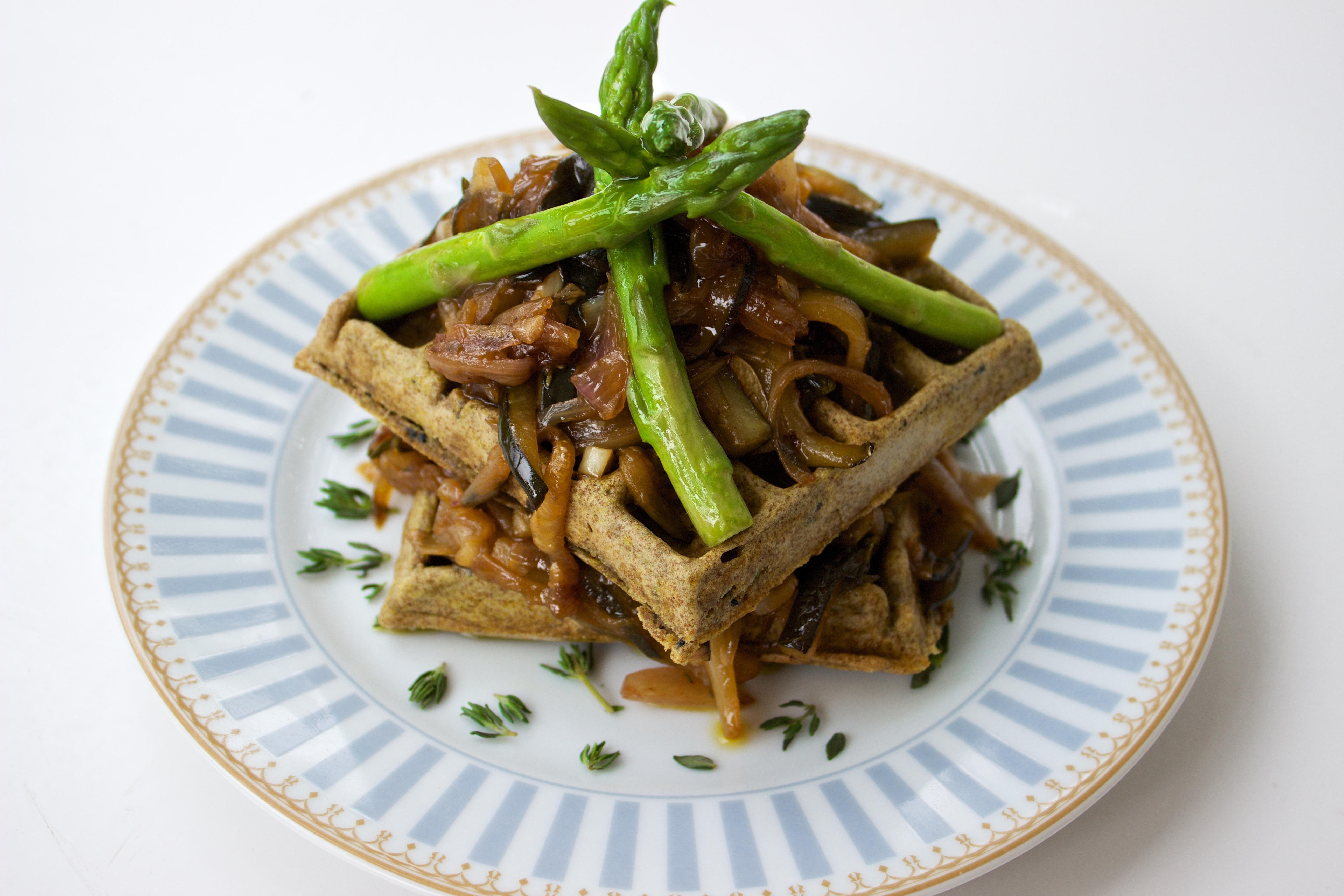 savoury waffles with asparagus on a blue plate and white background