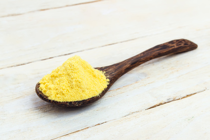 Asafoetida powder in wooden spoon on a white table