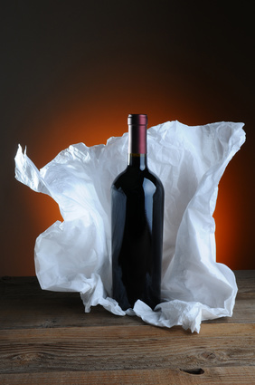 Red Wine Bottle with tissue paper wrapping on wood surface and light to dark warm background.