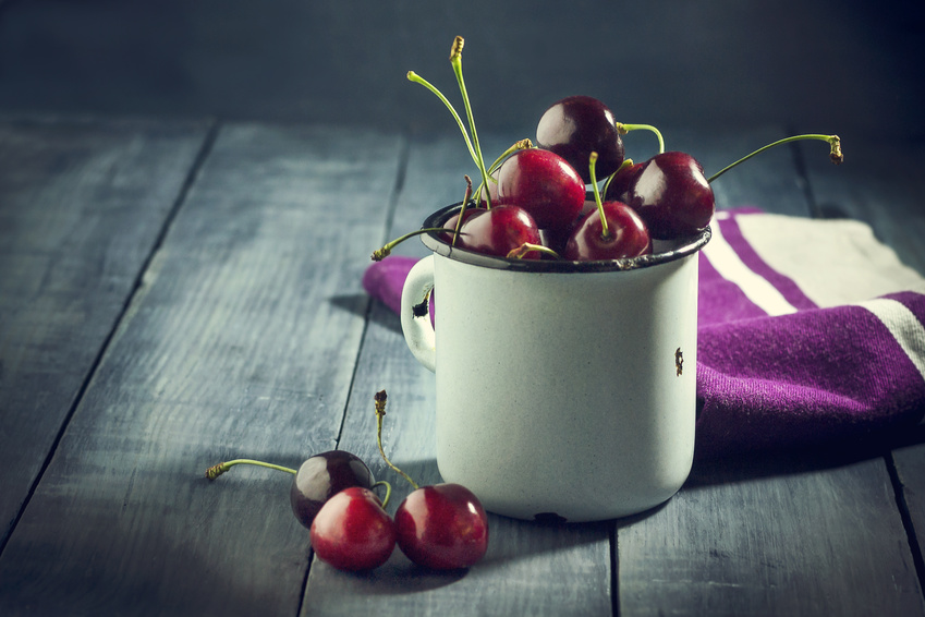 Ripe cherries in an iron mug on a dark blue wooden background. With copy space.